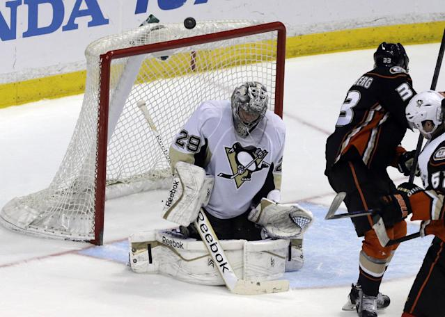 Pittsburgh Penguins goalie Marc-Andre Fleury (29) blocks the puck with Anaheim Ducks right winger Jakob Silfverberg (33), of Sweden, at right in the second period of an NHL hockey game in Anaheim, Calif., Friday, March 7, 2014. (AP Photo/Reed Saxon)