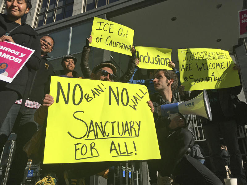 Protesters hold up signs outside a courthouse where a federal judge will hear arguments in the first lawsuit challenging President Donald Trump's executive order to withhold funding from communities that limit cooperation with immigration authorities Friday, April 14, 2017, in San Francisco. U.S. District Court Judge William Orrick has scheduled a hearing on Friday on San Francisco's request for a court order blocking the Trump administration from cutting off funds to any of the nation's so-called sanctuary cities. (AP Photo/Haven Daley)