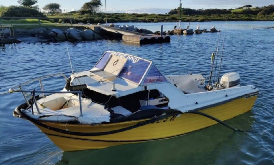The damaged boat in at a boat ramp.