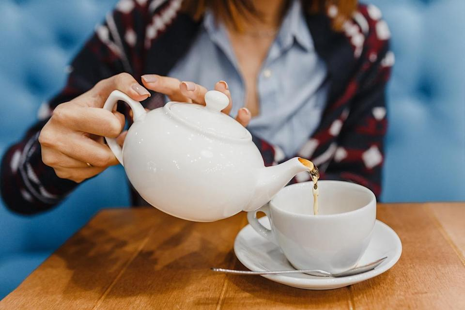 Person pours tea from a kettle close up shot