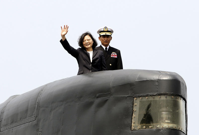 "FILE - In this March 21, 2017, file photo, Taiwan's President Tsai Ing-wen, left, waves from a Zwaardvis-class submarine during a visit at Zuoying Naval base in Kaohsiung, southern Taiwan. China says attempts by Taiwan's government to block its goal of bringing the self-governing island under Beijing's control are like ""stretching out an arm to block a car."" The new rhetorical broadside was launched late Tuesday, March 12, 2019 against Taiwanese President Tsai following her announcement of guidelines to counter China's ""one country, two systems"" framework for political unification with the island. (AP Photo/ Chiang Ying-ying, File)"
