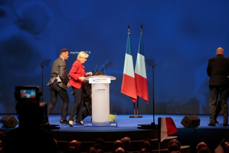 French presidential election candidate for the far-right Front National party Marine Le Pen (2nd L) stands next to her desk on stage as members of the security stop a protester interrupting her speech during a campaign meeting on April 17, 2017