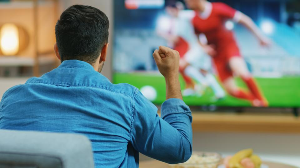 At Home Sports Fan Watches Important Soccer Match on TV, He Aggressively Clenches the Fist, Cheering for His Team. Cozy Living Room with Snacks and Drinks on the Table.