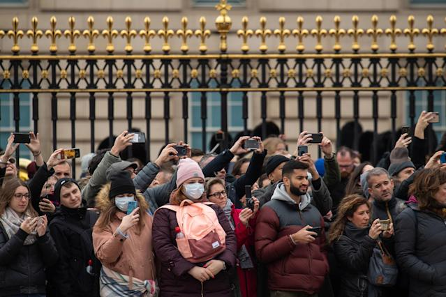 Two women wearing protective face masks stand amongst tourists watching the Changing of the Guard ceremony outside Buckingham Palace, London. (AP)