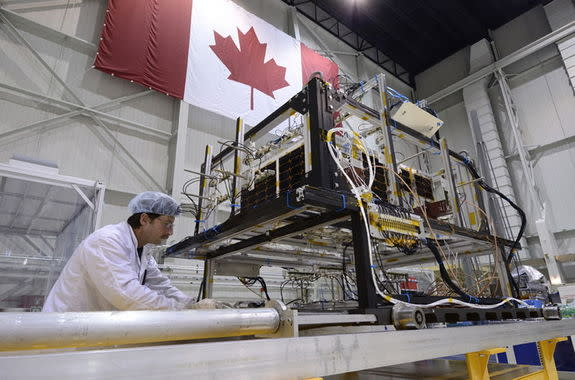 A technician removes the infrared test rig surrounding the asteroid-hunting NEOSSat after the final thermal vacuum test at the David Florida Laboratory located in Ottawa, Ontario. NEOSSat is a dual-mission microsatellite designed to detect pot