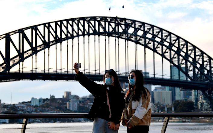 Pedestrians take time out for a selfie along Sydney Harbour - SAEED KHAN/AFP