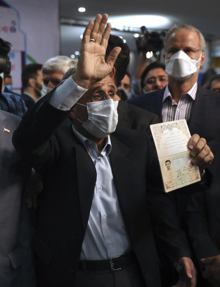 Former President Mahmoud Ahmadinejad waves as he shows his identification document while registering his name as a candidate for the June 18, presidential elections at elections headquarters of the Interior Ministry in Tehran, Iran, Wednesday, May 12, 2021. The country's former firebrand president will run again for office in upcoming elections in June. The Holocaust-denying Ahmadinejad has previously been banned from running for the presidency by Supreme Leader Ayatollah Ali Khamenei in 2017, although then, he registered anyway. (AP Photo/Vahid Salemi)
