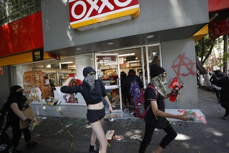 Anarchist protesters loot a convenience store before going to attack a security barrier around the nearby U.S. Embassy, in Mexico City, Friday, June 5, 2020. Following the recent deaths of George Floyd and Giovanni Lopez after encounters with U.S. and Mexican police, anarchist protesters who are known for their violent tactics attacked a barrier outside the U.S. Embassy, smashed store fronts and looted convenience stores, before clashing with police in an upscale neighborhood.(AP Photo/Rebecca Blackwell)