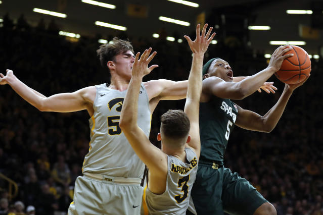 Michigan State guard Cassius Winston, right, drives to the basket over Iowa's Luka Garza, left, and Jordan Bohannon (3) during the first half of an NCAA college basketball game Thursday, Jan. 24, 2019, in Iowa City, Iowa. (AP Photo/Charlie Neibergall)