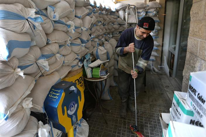 A Lebanese worker cleans next to sand barriers that were set in front of a shop, in a Shiite neighborhood of a southern suburb of Beirut, Lebanon, Tuesday, Jan. 28, 2014. After a wave of car bomb attacks on Hezbollah's stronghold south of Beirut that left scores of people dead or wounded over the past three months, shop owners scared of more bombs have set up sand barriers in front of their institutions to reduce damage in case more blasts occur. The attacks that hit the south Beirut area known as Dahiyeh (suburb) has sacred many people in the area and increased security measures by Lebanese troops and members of the militant group.(AP Photo/Hussein Malla)
