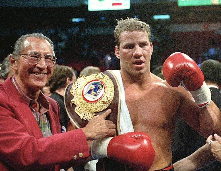 """FILE - In this June 7, 1993 file photo, newly crowned WBO heavyweight champion Tommy Morrison receives his championship belt after defeating George Foreman in Las Vegas, Nev. Morrison, a former heavyweight champion who gained fame for his role in the movie """"Rocky V,"""" has died. He was 44. Morrison's former manager, Tony Holden says his longtime friend died Sunday night, Sept. 1, 2013, at a Nebraska hospital. (AP Photo/Nick Ut, File)"""