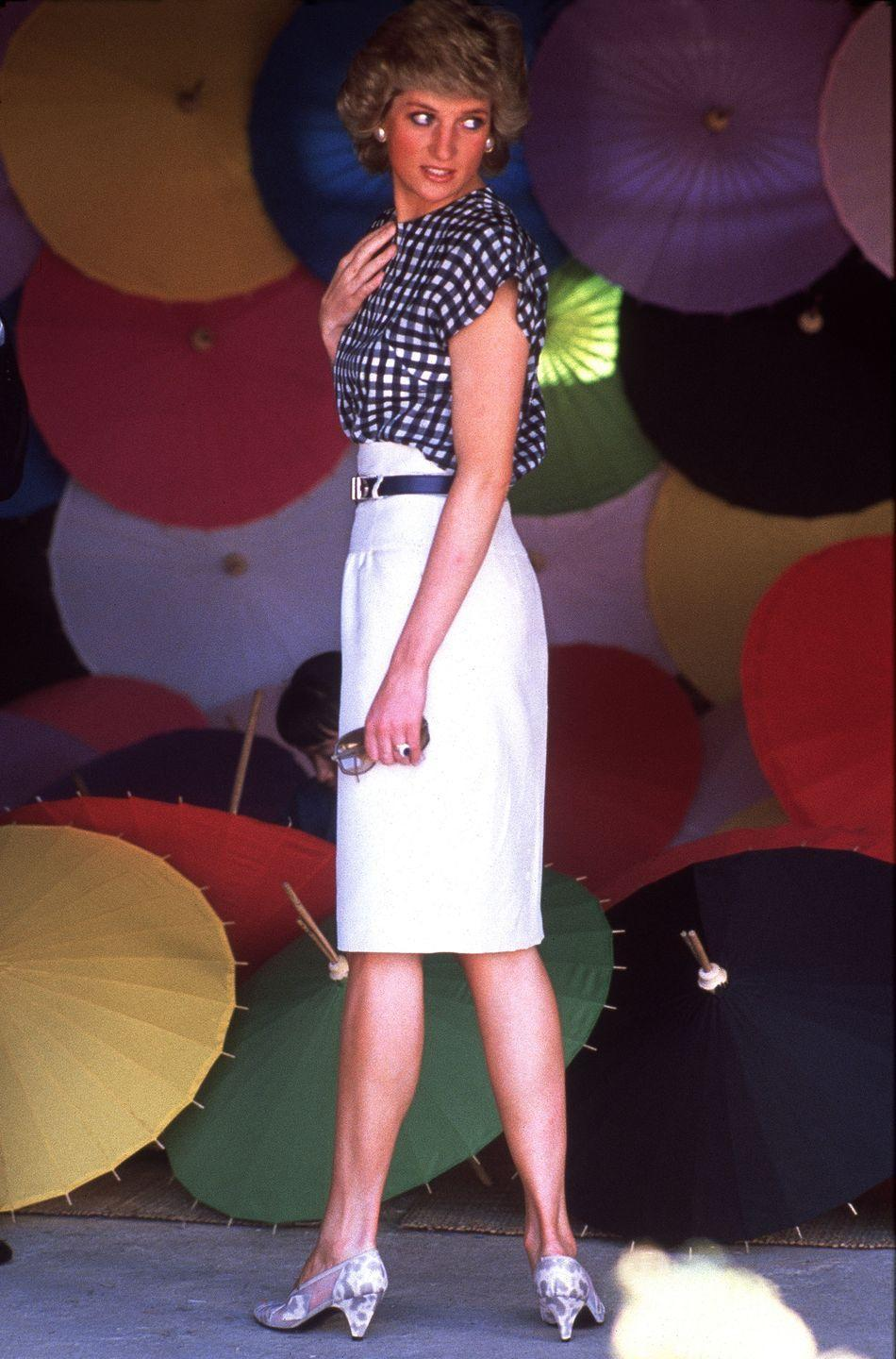 <p>In a gingham shirt paired with a white skirt by Alistair Blair at an umbrella factory during the official visit to Thailand. </p>