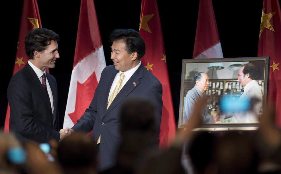 Prime Minister Justin Trudeau shakes hands with China's Ambassador to Canada Luo Zhaohui (right) after being presented a photo of his father, former Prime Minister Pierre Elliot Trudeau, meeting Chairman Mao Zedong, during a celebration of 45 years of Canada-China diplomatic relations, in Ottawa on Jan. 27, 2016. THE CANADIAN PRESS/Justin Tang