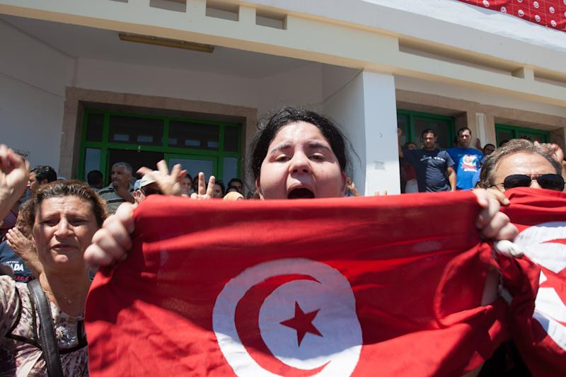 In this photo dated Thursday, July 25, 2013, assassinated Tunisian opposition politician Mohammed Brahmi's daughter, Balkis, holds a Tunisian flag as she mourns his death at Mahmoud Materi hospital, north of Tunis, Tunisia. Her father was in his car outside his home when gunmen fired several shots at him, said Interior Ministry spokesman Mohammed Ali Aroui. It is the second killing of an opposition member this year, following that of Chokri Belaid, a member of the same leftist Popular Front coalition as Brahmi. (AP Photo/Amine Landoulsi)