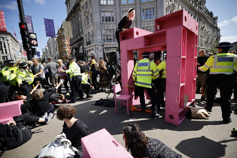 Police officers arrive as climate activists from the Extinction Rebellion group build a structure and set up lock-on devices blocking the road in the middle of Oxford Circus in central London on August 25, 2021 during the group's 'Impossible Rebellion' series of actions. - Climate change demonstrators from environmental activist group Extinction Rebellion continued with their latest round of protests in central London, promising two weeks of disruption. (Photo by Tolga Akmen / AFP) (Photo by TOLGA AKMEN/AFP via Getty Images)