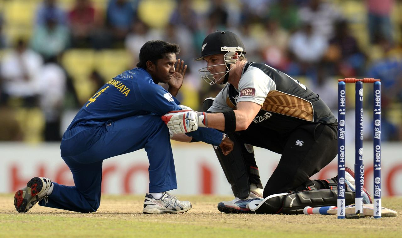 Sri Lanka's Akila Dhananjaya is helped by New Zealand's Brendon McCullum (R) after being hit in the face by the ball during the Twenty20 World Cup Super 8 match at Pallekele in Sri Lanka September 27, 2012. REUTERS/Philip Brown (SRI LANKA - Tags: SPORT CRICKET)
