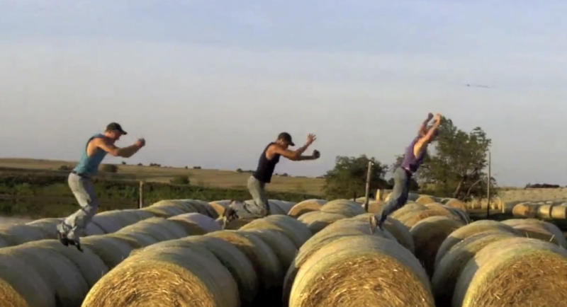 "This frame grab from video shows Assaria, Kan., brothers, from left: Nathan; Kendal and Greg Peterson in their video parody on LMAFO's ""Sexy and I Know It."" The parody, that has gone viral on YouTube and Facebook, shows the three brothers rapping their farming mission on the family's Saline County farm. (AP Photo/Courtesy Greg Peterson)"