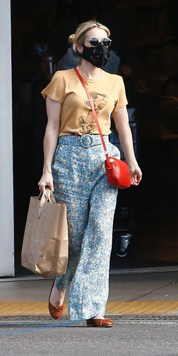 """<p>Emma Roberts was as cute as ever in a pair of wide-leg printed pants (<strong>Shop similar:</strong> $119; <a href=""""https://click.linksynergy.com/deeplink?id=93xLBvPhAeE&mid=1237&murl=https%3A%2F%2Fshop.nordstrom.com%2Fs%2Fpolo-ralph-lauren-floral-satin-wide-leg-pants%2F5500221&u1=IS%2CEmmaRoberts%2Canesta%2C%2CIMA%2C3547773%2C202005%2CI"""" rel=""""nofollow noopener"""" target=""""_blank"""" data-ylk=""""slk:nordstrom.com"""" class=""""link rapid-noclick-resp"""">nordstrom.com</a>), Peanuts t-shirt (<strong>Shop similar: </strong>$50; <a href=""""http://www.anrdoezrs.net/links/7799179/type/dlg/sid/IS%2CEmmaRoberts%2Canesta%2C%2CIMA%2C3547773%2C202005%2CI/https://www.jcrew.com/us/p/mens_category/tshirts/peanuts-x-jcrew-shortsleeve-surfer-snoopy-tshirt/AK489"""" rel=""""nofollow noopener"""" target=""""_blank"""" data-ylk=""""slk:jcrew.com"""" class=""""link rapid-noclick-resp"""">jcrew.com</a>), and red crossbody bag (<strong>Shop similar: </strong>$178; <a href=""""https://shareasale.com/r.cfm?b=1149061&u=1772040&m=78153&urllink=https%3A//www.hobobags.com/products/evoke-rio-leather-crossbody%3F_pos%3D6%26_sid%3D84a9d549c%26_ss%3Dr&afftrack=IS%252CEmmaRoberts%252Canesta%252C%252CIMA%252C3547773%252C202005%252CI"""" rel=""""nofollow noopener"""" target=""""_blank"""" data-ylk=""""slk:hobobags.com"""" class=""""link rapid-noclick-resp"""">hobobags.com</a>).</p>"""