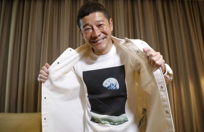 Japanese billionaire Yusaku Maezawa poses with his T-shirt bearing an image of Earth during an interview with Reuters in Tokyo