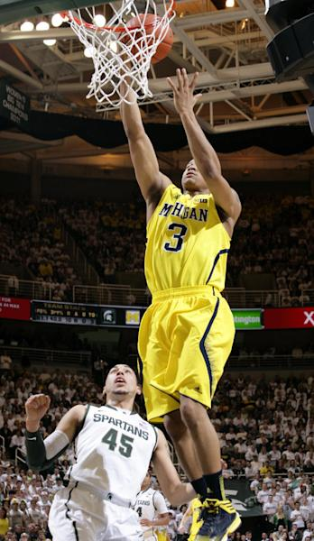 Michigan's Trey Burke (3) shoots a layup after getting a steal against Michigan State's Denzel Valentine (45) during the first half of an NCAA college basketball game, Tuesday, Feb. 12, 2013, in East Lansing, Mich. (AP Photo/Al Goldis)