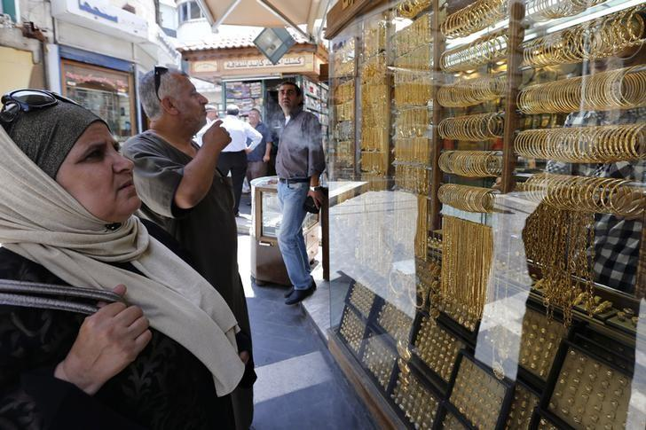 Customers look at gold jewellery displayed at a shop in Amman