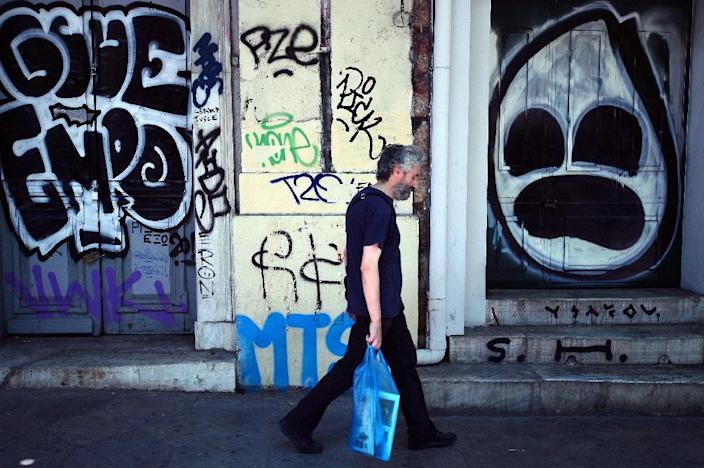 A man walks past stores shut down and covered with graffiti in central Athens on August 11, 2015 (AFP Photo/Louisa Gouliamaki)