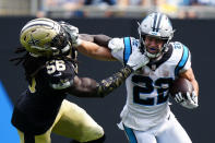 Carolina Panthers running back Christian McCaffrey pushes away from New Orleans Saints outside linebacker Demario Davis during the second half of an NFL football game Sunday, Sept. 19, 2021, in Charlotte, N.C. (AP Photo/Jacob Kupferman)