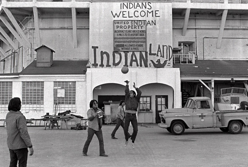 FILE - In this Nov. 26, 1969, file photo, Native Americans play ball games at the main dock area on Alcatraz in San Francisco during their occupation of the island. The week of Nov. 18, 2019, marks 50 years since the beginning of a months-long Native American occupation at Alcatraz Island in the San Francisco Bay. The demonstration by dozens of tribal members had lasting effects for tribes, raising awareness of life on and off reservations, galvanizing activists and spurring a shift in federal policy toward self-determination. (AP Photo/File)