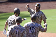 San Diego Padres' Wil Myers (4) is congratulated by Eric Hosmer (30), Jake Cronenworth (9) and Mitch Moreland (18) after hitting a three-run home run during the sixth inning of a baseball game against the Seattle Mariners Sunday, Sept. 20, 2020, in San Diego. (AP Photo/Denis Poroy)
