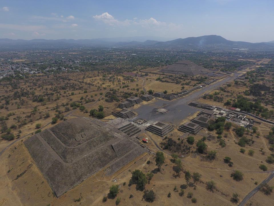 FILE - In this March 19, 2020 file photo, the Pyramid of the Moon, left, and the Pyramid of the Sun, back right, are seen along with smaller structures lining the Avenue of the Dead, in Teotihuacan, Mexico. The Mexican government said Tuesday, May 25, 2021, that a private building project is destroying part of the outskirts of the pre-Hispanic ruin site of Teotihuacan, just north of Mexico City. (AP Photo/Rebecca Blackwell, File)