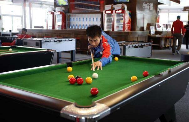 Boxer Pak Jong Chol of North Korea plays pool at the Athletes' Village at the Olympic Park in London, July 19, 2012.