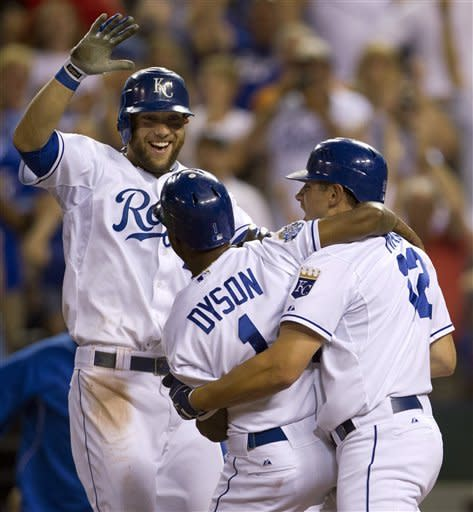 Kansas City Royals' Jarrod Dyson (1) is congratulated by teammates Alex Gordon, left, and Mitch Maier (12) after scoring the winning run of a baseball game against the Milwaukee Brewers at Kauffman Stadium in Kansas City, Mo., Thursday, June 14, 2012. The Royals defeated the Brewers 4-3. (AP Photo/Orlin Wagner)
