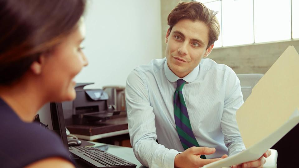 Young male professional shows documents to woman in meeting.