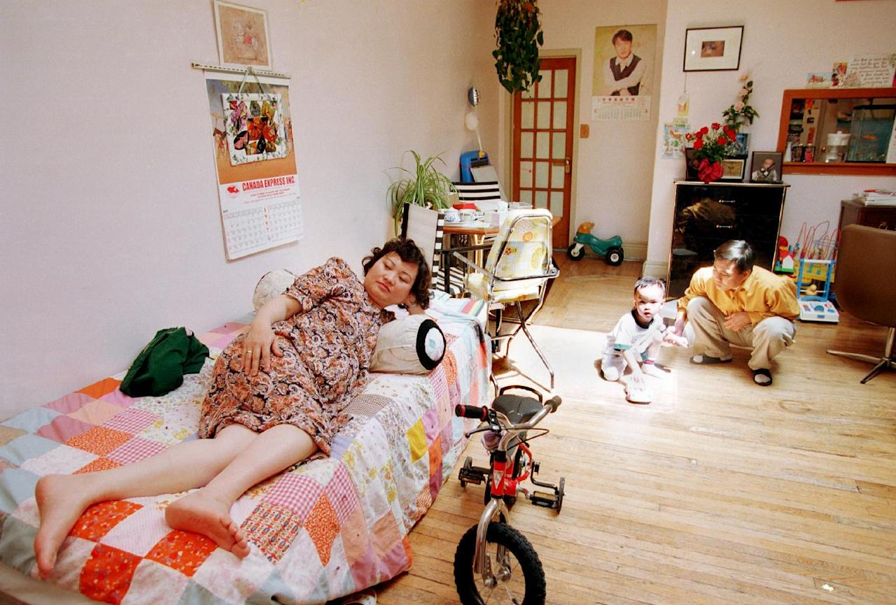 FILE - In this June 8, 1992 file photo, Phan Thi Kim Phuc, left, watches television as her husband, Bui Huy Toan, plays with their son Thomas, 3, in their apartment in Toronto. Phuc, who was the main subject in Associated Press photographer Nick Ut's iconic image of the aftermath of a June 8, 1972 napalm attack in Vietnam, was granted political asylum in Canada in 1992. (AP Photo/Nick Ut)