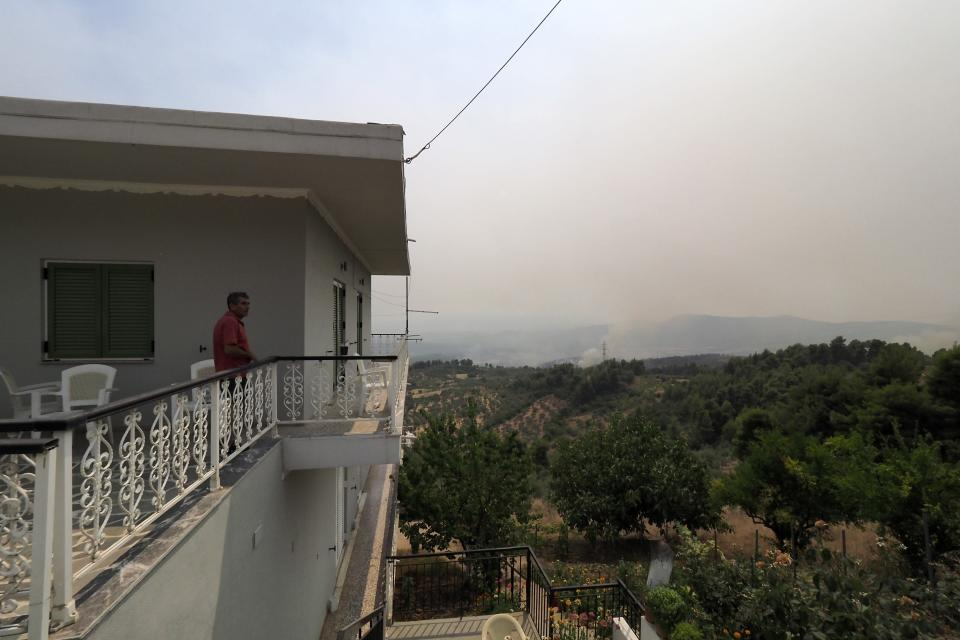A local resident watches from his balcony the wildfire in Kourkouloi village on the island of Evia, about 150 kilometers (93 miles) north of Athens, Greece, Thursday, Aug. 5, 2021. Forest fires fueled by a protracted heat wave raged overnight and into Thursday in Greece, threatening the archaeological site at the birthplace of the modern Olympics and forcing the evacuation of dozens of villages. (AP Photo/Thodoris Nikolaou)