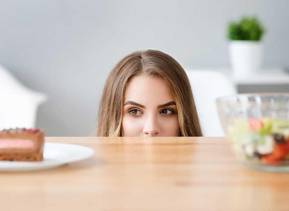 Woman craving junk food over salad