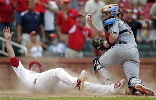 St. Louis Cardinals' David Freese (23) looks for the call as Miami Marlins catcher John Buck shows the ball in the ninth inning of a baseball game, Sunday, July 8, 2012, in St. Louis. Freese scored from second on a single by Rafael Furcal as the Cardinals won 5-4. (AP Photo/Tom Gannam)