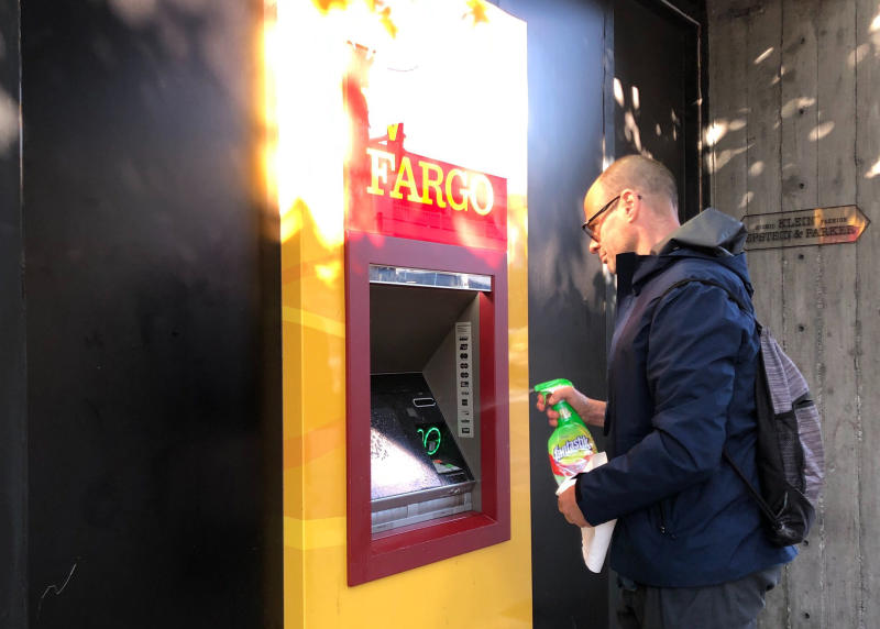 David Mayer, a personal trainer and yoga instructor in San Francisco, sprays down a Wells Fargo ATM machine before using it in San Francisco on Friday, March 20, 2020. Nearly 40 million people in California awoke Friday to the reality of a near lockdown to prevent the spread of coronavirus. (AP Photo/Olga R. Rodriguez)