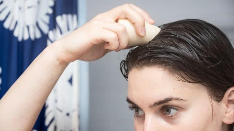 Lather the shampoo bar in your hands or directly on your head.
