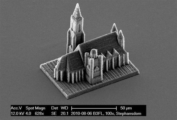 """A handout electron microscope photograph shows a nano-scale model of Vienna's St. Stephans cathedral created by a newly developed 3D printing technique for nano structures, made available to Reuters March 29, 2012. Researchers from the Vienna University of Technology have set a new world speed record for creating 3D nano objects. The University team create their grain of sand-size structures in just four minutes, a fraction of the time that other items have previously been printed. Previously making complex large 3D structures would take hours or even days but with the newly developed 3D laser printer the scientists can speed that up by a factor of 500 or in some cases 1,000 times. The process called """"two-photon lithography"""" involves using a focused laser beam to harden liquid resin in order to create micro objects of solid polymer. The scientists said the technique could be developed to make small biomedical parts to be used by doctors."""