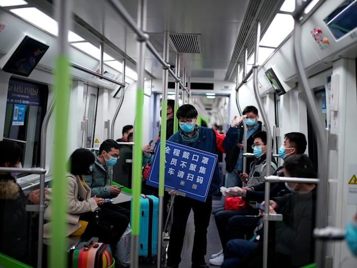 A staff member holds a placard while standing among passengers on a subway train after service resumed in Wuhan on March 28, 2020.