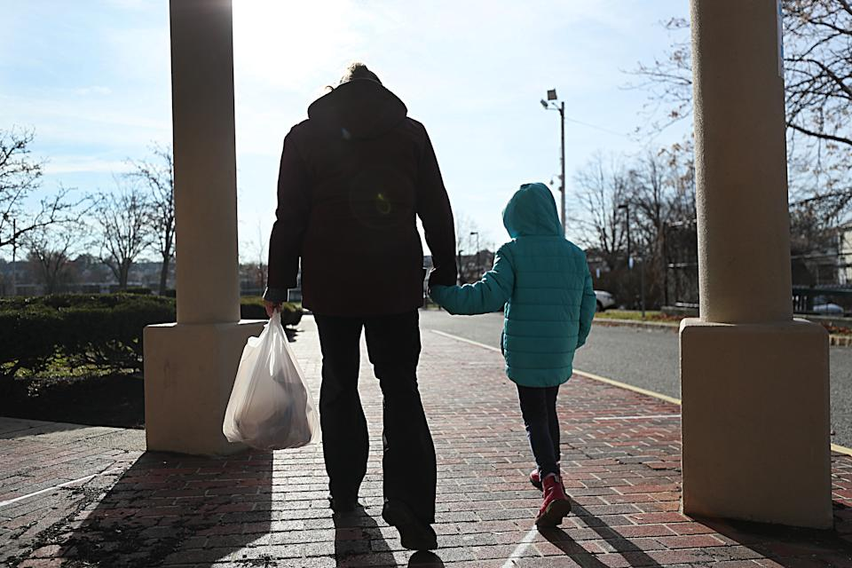 BOSTON - DECEMBER 11: A woman and her daughter walk from  her elementary school after picking  up her breakfast and lunch in Revere, MA on Dec. 11, 2020. She is among many low-income parents in Massachusetts who have struggled to receive their promised free school meals during the pandemic. Her daughter's school offers meal pick-up from 10:30a.m. to 1 p.m., but her daughter only has a break from classes from 10:50 to 11:30, and so the single mother must strap her daughter in a jogging stroller and rush to the school a half-mile away since they don't have a car to pick up meals. (Photo by Suzanne Kreiter/The Boston Globe via Getty Images)
