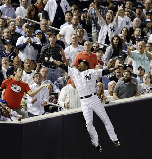 Fans watch as New York Yankees left fielder Dewayne Wise catches a seventh-inning flyout to left field hit by Cleveland Indians' Jack Hannahan during their baseball game at Yankee Stadium in New York, Tuesday, June 26, 2012. (AP Photo/Kathy Willens)