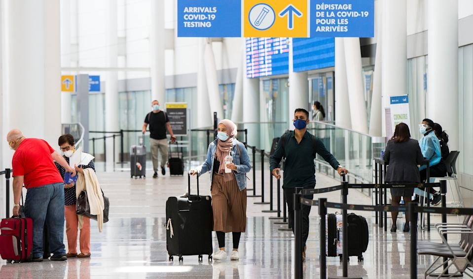 """Travelers wearing face masks walk out of the arrivals hall at Toronto Pearson International Airport in Mississauga, Ontario, Canada, on July 5, 2021. Starting from Monday, """"fully vaccinated"""" Canadians and permanent residents can enter Canada without undergoing quarantine. (Photo by Zou Zheng/Xinhua via Getty Images)"""