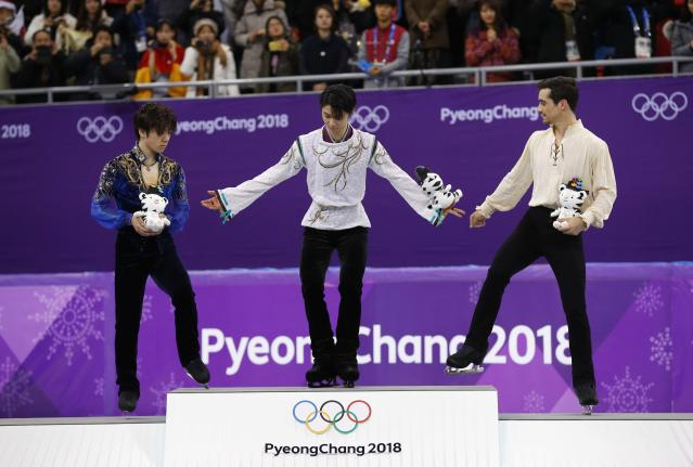 Figure Skating - Pyeongchang 2018 Winter Olympics - Men Single free skating competition final - Gangneung, South Korea - February 17, 2018 - Gold medallist Yuzuru Hanyu of Japan, silver medallist Shoma Uno of Japan and bronze medallist Javier Fernandez of Spain celebrate on the podium. REUTERS/Phil Noble