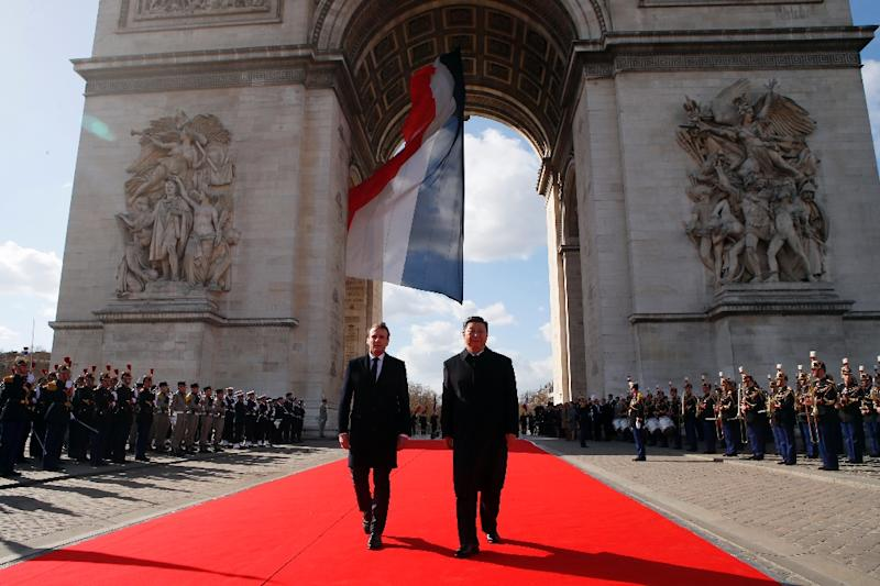 French President Emmanuel Macron, left, and Chinese President Xi Jinping laid a wreath before the eternal flame at the Arc de Triomphe in Paris on Monday (AFP Photo/Francois Mori)