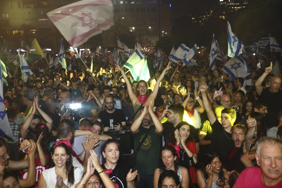Israelis celebrate the swearing in of the new government in Tel Aviv, Israel, Sunday, June 13, 2021. Israel's parliament has voted in favor of a new coalition government, formally ending Prime Minister Benjamin Netanyahu's historic 12-year rule. Naftali Bennett, a former ally of Netanyahu became the new prime minister. (AP Photo/Oded Balilty)