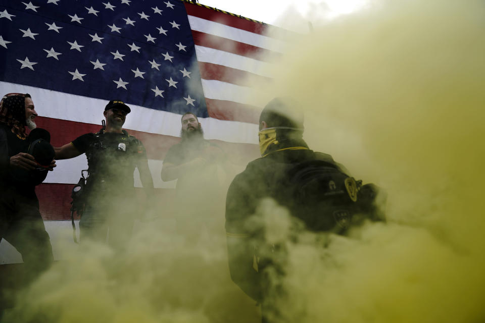 Members of the Proud Boys speak on stage as smoke flies in the air at a rally with other right-wing demonstrators on Saturday, Sept. 26, 2020, in Portland, Ore. (AP Photo/John Locher)