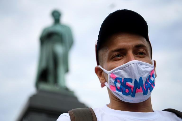 "A man protesting against the changes wears a facemask emblazoned with the word ""Deception"""