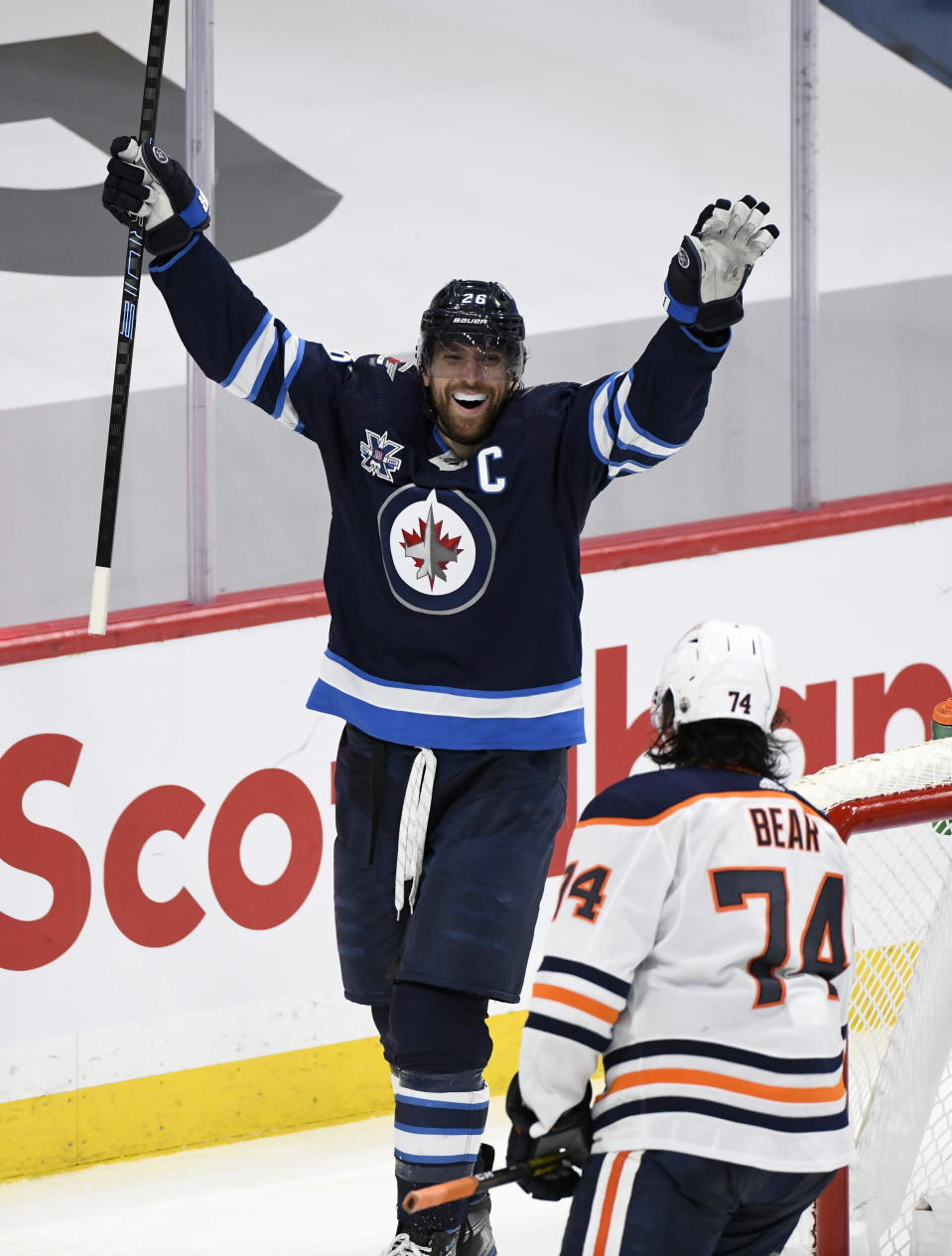 Winnipeg Jets' Blake Wheeler (26) celebrates a goal by Mark Scheifele during the third period of an NHL hockey Stanley Cup playoff game against the Edmonton Oilers, Monday, May 24, 2021, in Winnipeg, Manitoba. (Fred Greenslade/The Canadian Press via AP)
